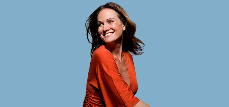 Woman smiling and looking behind her against blue background