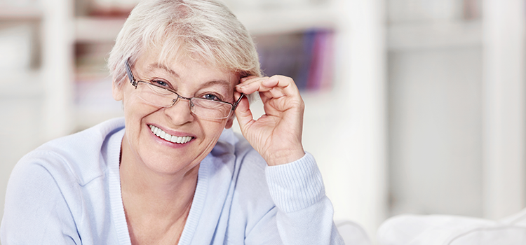 Smiling middle aged woman adjusting her glasses