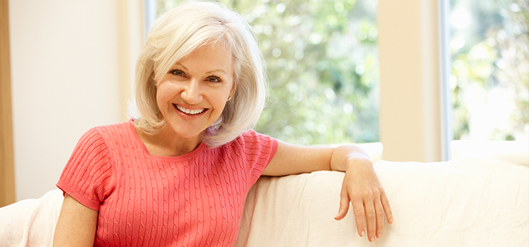 Middle aged woman smiling and sitting casually on white sofa in home
