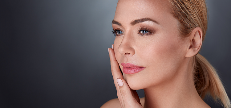 Woman with smooth skin looking pensive with hand on her face