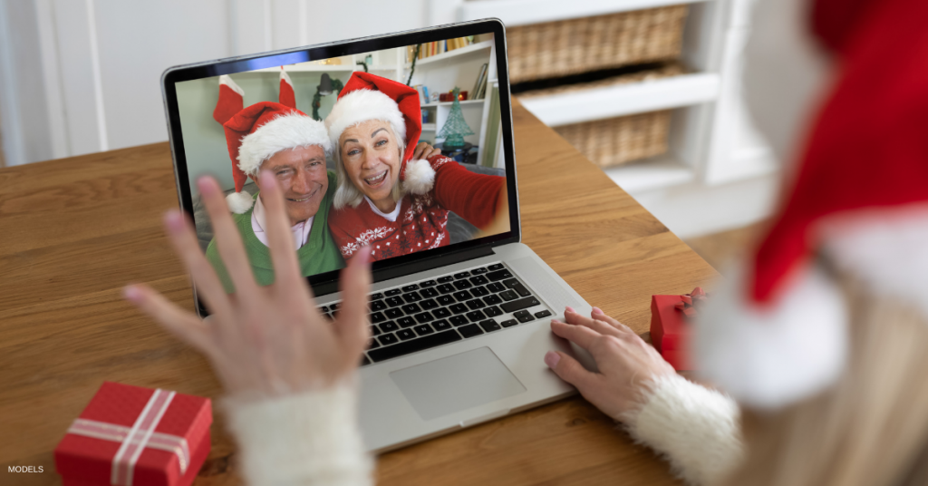 Woman in santa hat waving while having a videocall with senior couple in santa hats on laptop at home.